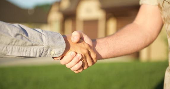 Military men shaking hands outside home   Veterans United