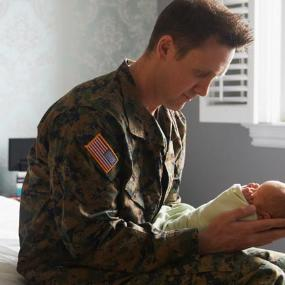 Military father holding his newborn baby | LWA/Dann Tardif/Getty Images