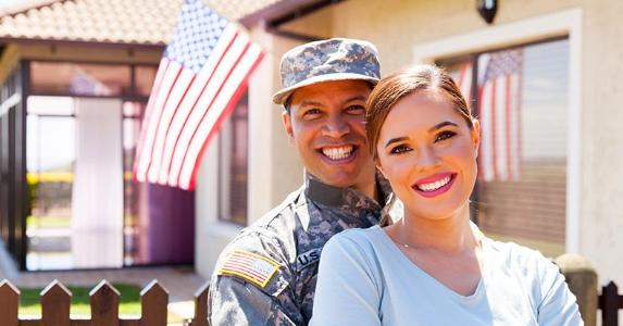 Military man and wife standing outside house | michaeljung/Shutterstock.com