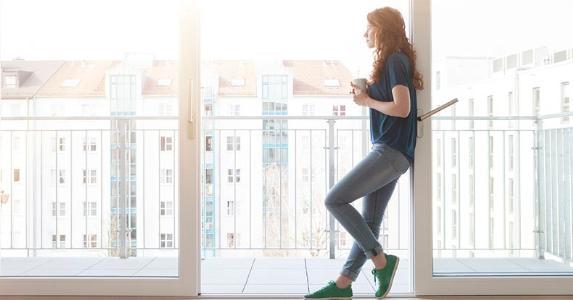 Millennial standing in frame of patio doorway   Westend61/Getty Images