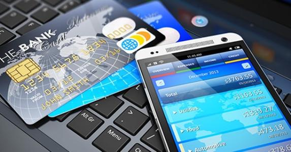 Mobile banking app and credit cards on keyboard © Oleksiy Mark/Shutterstock.com