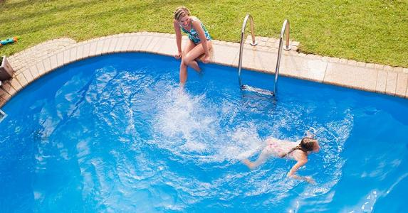Mom and daughter in backyard pool | Westend61/Getty Images