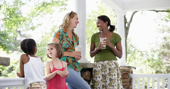 Moms and daughters on playdate in house's front porch | Sean Justice/Getty Images