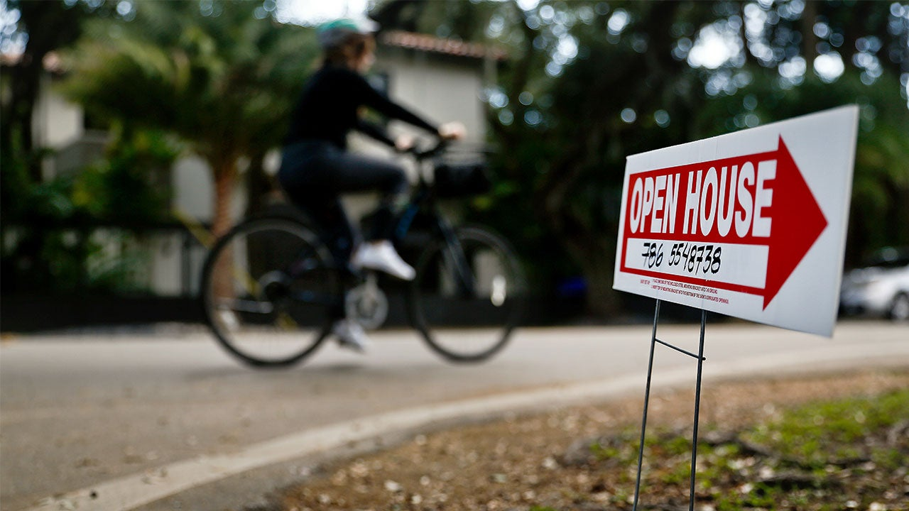 Person biking away from open house sign | Bloomberg/Getty Images