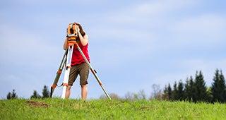 Woman surveying empty lot © l i g h t p o e t/Shutterstock.com