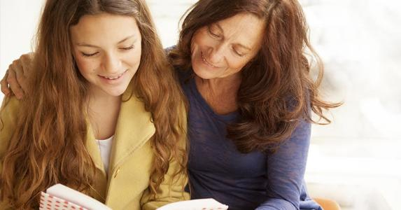 Mother and daughter reading a book | Brainsil/E+/Getty Images