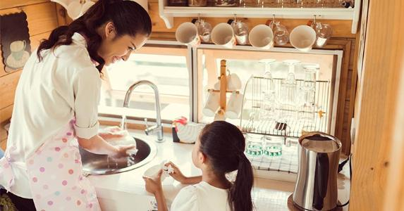 Mother and daughter washing dishes | TORWAISTUDIO/Shutterstock.com
