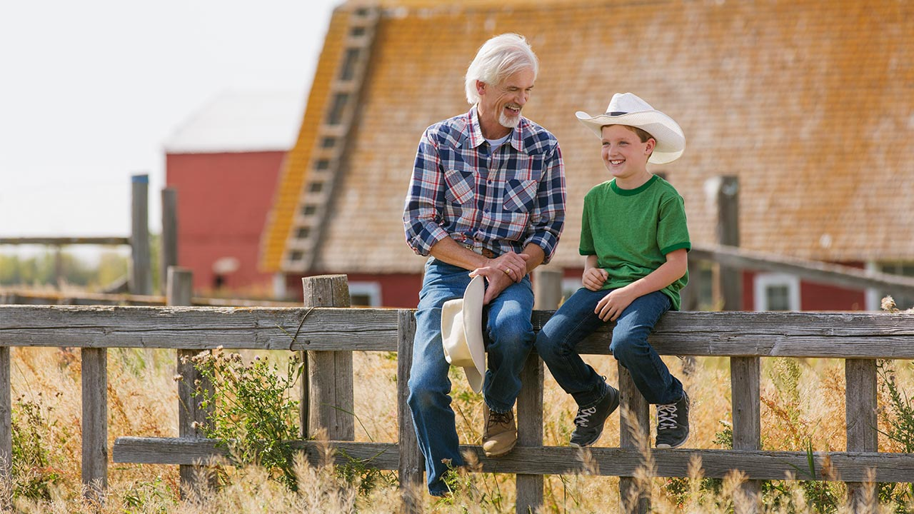 Mature man and boy sitting on fence outside barn | Hero Images/Getty Images