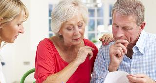 Older couple looking over document with adviser © Monkey Business Images/Shutterstock.com