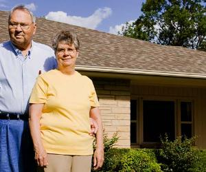 Homeowners standing in front of home © iStock