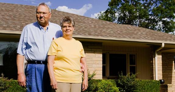 Homeowners standing in front of home | iStock.com/blueflames