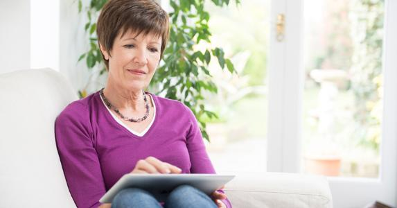 Older woman sitting with tablet on her lap © iStock