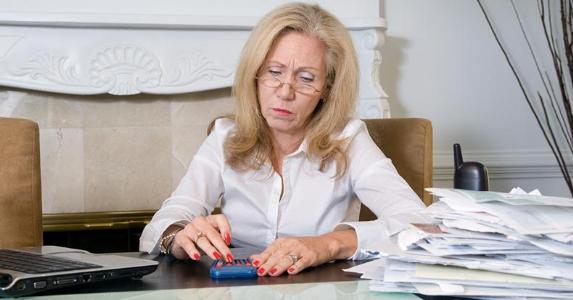 Woman using a calculator, budgeting © iStock