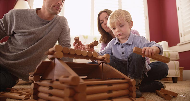 Parents building wooden cabin with child | Rocketclips, Inc./Shutterstock.com