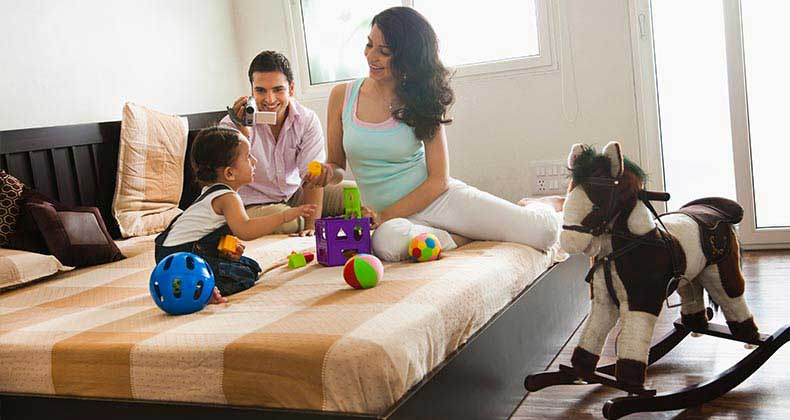 Parents playing with daughter in bedroom | ImagesBazaar/Getty Images