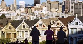 Pedestrians looking at houses in San Francisco | David Paul Morris/Bloomberg via Getty Images