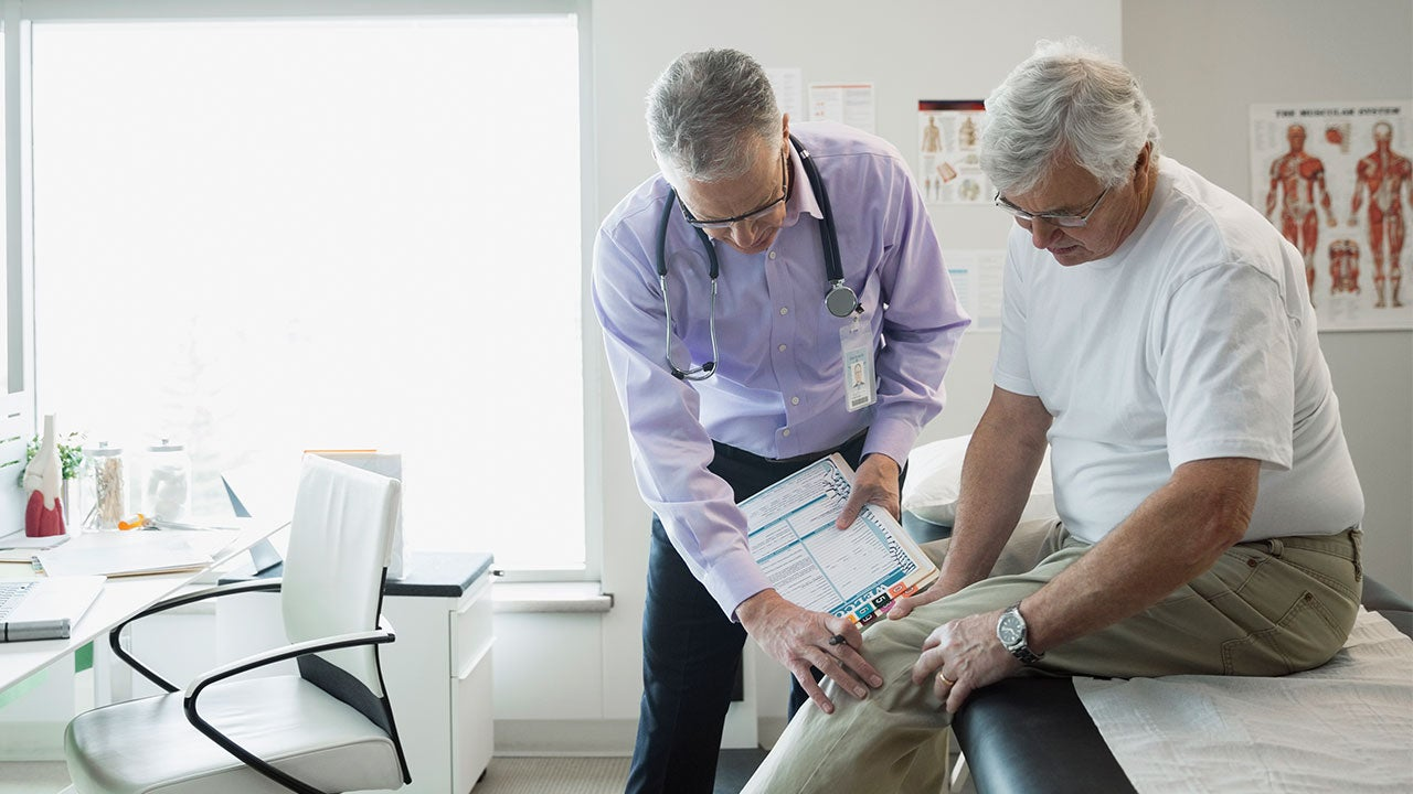 Doctor checking a man's knee   Hero Images/Getty Images