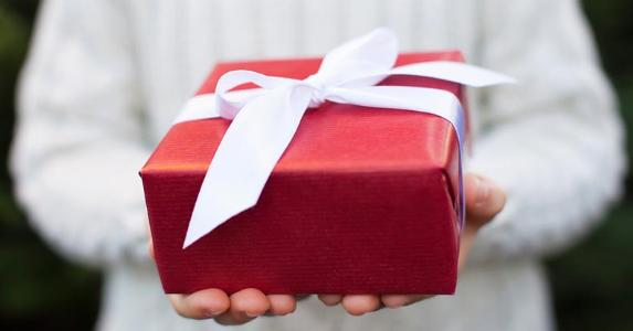 Person holding gift wrapped in red and white © iStock