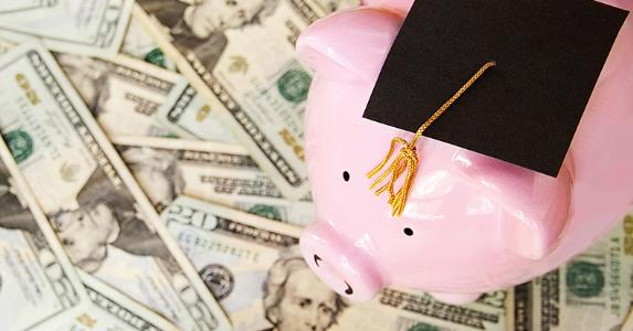 Piggy bank wearing graduation cap on top of $20 bills © zimmytws/Shutterstock.com