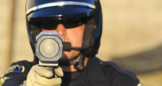 Police officer aiming radar gun © John Roman Images/Shutterstock.com