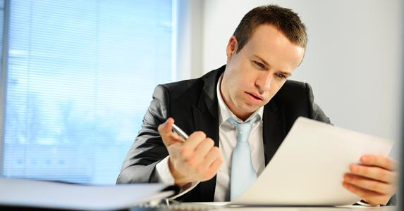 Professionally dressed man reading documents in office © iStock