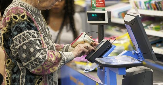 Woman signing for credit card purchase in grocery | Bloomberg/Getty Images