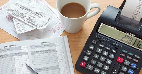Receipts with bookkeeping ledger and calculator © RTimages / Fotolia