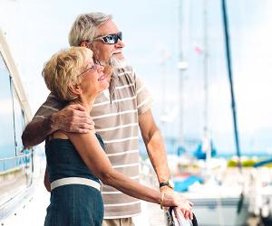 Retiree couple smiling, looking out from boat deck | Borut Trdina/E+/Getty Images