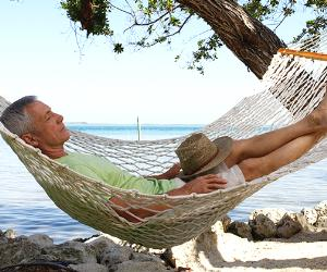 Retiree resting in hammock on the beach shore | Kraid Scarbinsky/DigitalVision/Getty Images