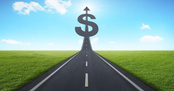 Road heading towards a dollar sign © iStock