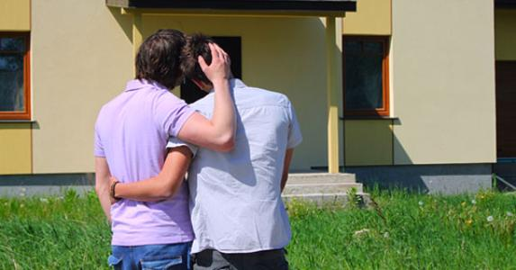 Same sex couple embracing in front of house © Karina Kononenko/Shutterstock.com