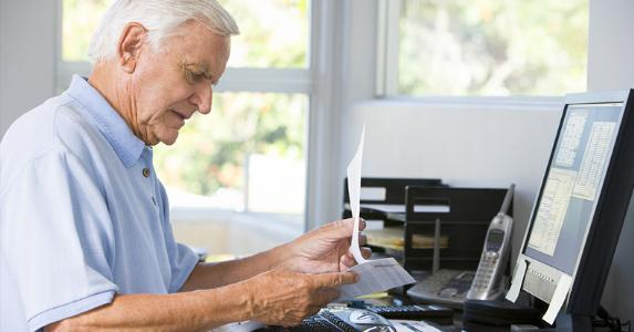 Senior at desk looking over paperwork © Monkey Business Images/Shutterstock.com