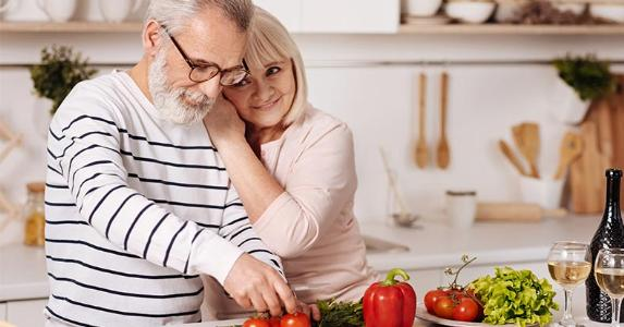 Senior couple hugging in kitchen | Dmytro Zinkevych/Shutterstock.com