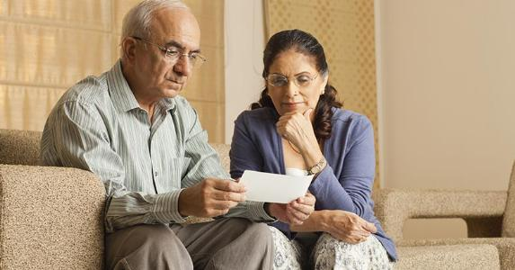 Senior couple reading a check | imagesBazaar/Brand X Pictures/Getty Images