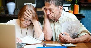 Senior couple with bills © CREATISTA/Shutterstock.com
