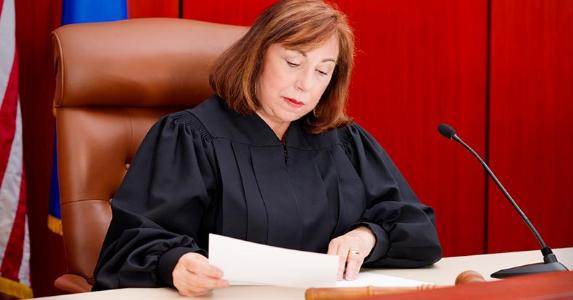 Senior female judge reading paperwork | iStock.com/Alina Solovyova-Vincent