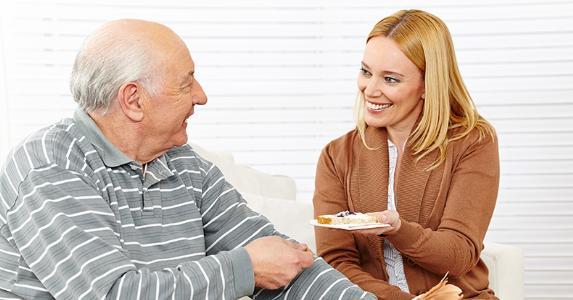 Senior man eating breakfast with assisted living home employee © Robert Kneschke/Shutterstock.com