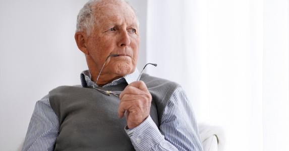 Senior man holding his glasses © iStock