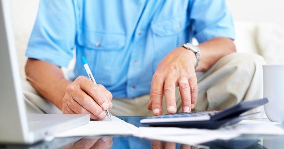 Senior man wearing blue shirt, calculating budget