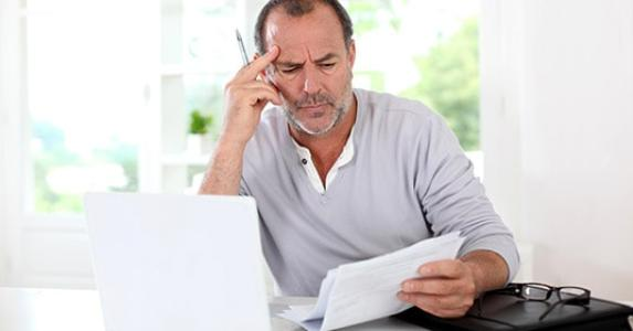 Senior man puzzled with tax document © Goodluz/Shutterstock.com