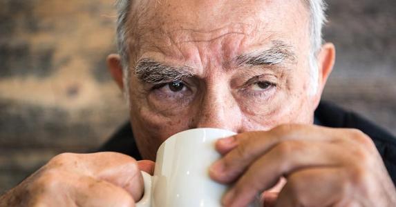 Senior man sipping from mug | Juanmonino/E+/Getty Images