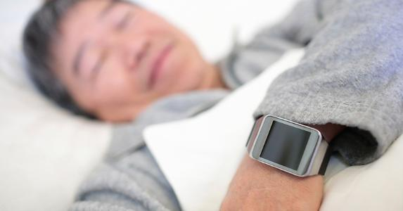 Man sleeping while wearing smartwatch © iStock