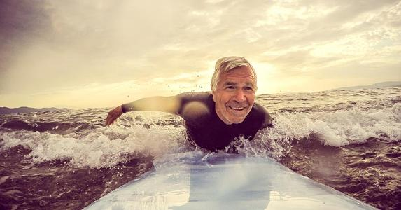 Senior man surfing on the ocean | Aleksandar Nakic/Getty Images