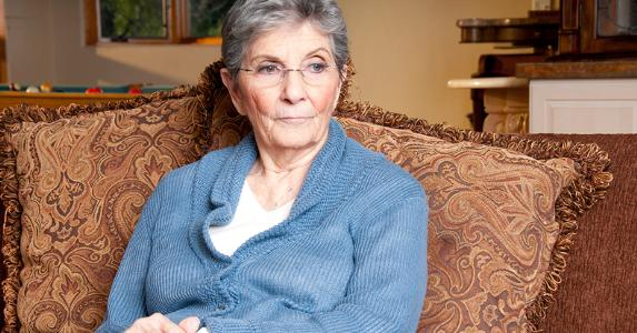 Senior woman seated on her couch