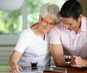 Senior woman drinking coffee with adult son at home © auremar/Shutterstock.com