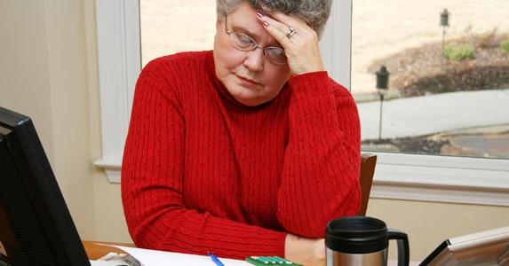 Senior woman in red sweater overwhelmed with bills | iStock.com/killerb10