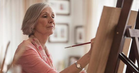 Senior woman painting at home | Jose Luis Pelaez Inc/Getty Images