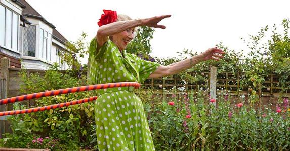 Senior woman in polka dot dress hula-hooping | David Woolley/Getty Images