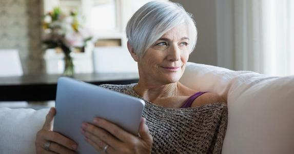 Senior woman holding a tablet, looking right | Hero Images/Getty Images