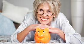 Happy senior woman posing with orange piggy bank © racorn/Shutterstock.com